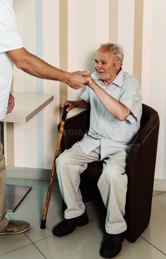 Der Doktor, der einem alten Mann hilft, stehen auf lizenzfreies stockbild