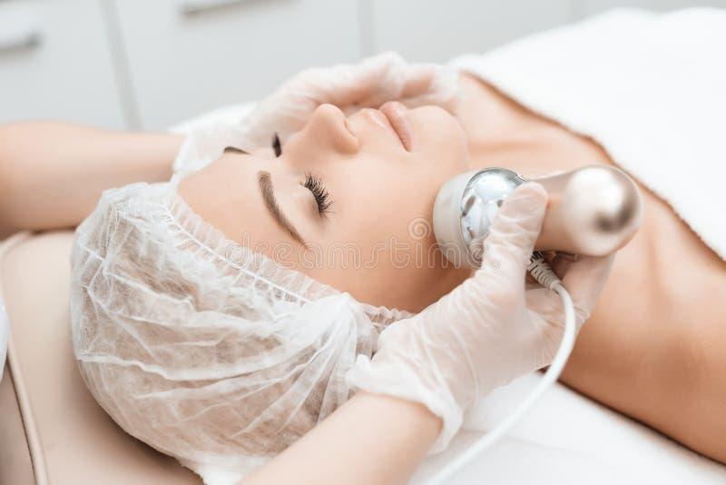 Der Doktor fährt das Mädchen angesichts des photoepilator Das Mädchen kam zum Verfahren für Laser-Haarabbau stockfotos