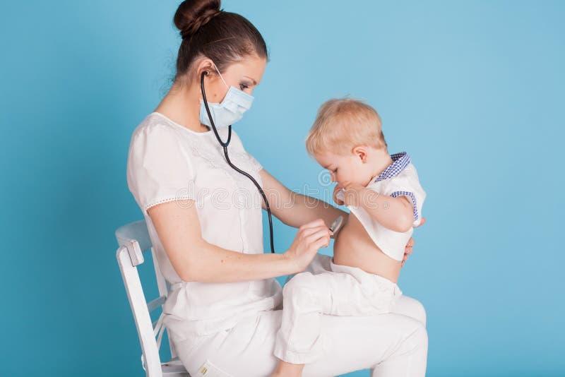 Der Doktor hört auf das Stethoskop des kleinen Jungen lizenzfreies stockfoto