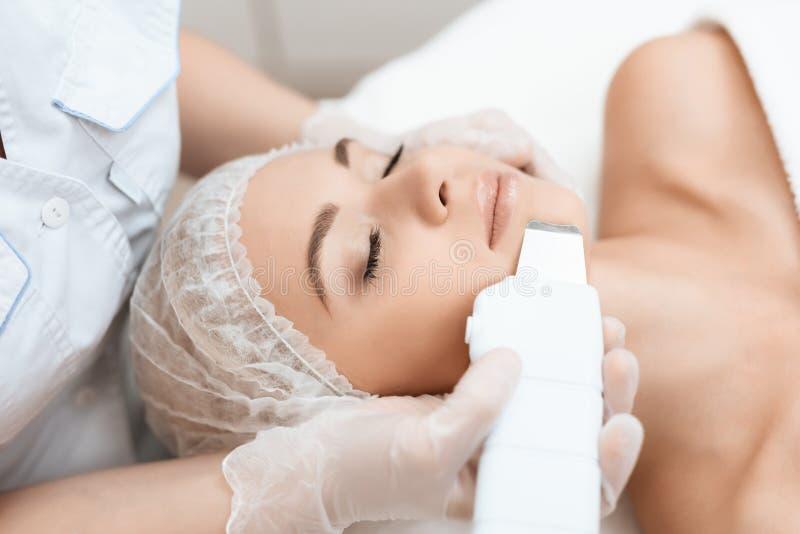 Der Doktor reinigt die Frau ` s Haut mit einem speziellen medizinischen Gerät Die Frau kam zum Verfahren des Laser-Haarabbaus lizenzfreies stockfoto