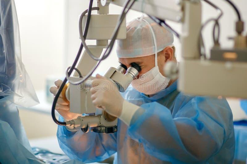 Der Doktor schaut durch ein Mikroskop, das aphtholmologist durchführt eine Operation auf den Augen, ein Wissenschaftler überprüft lizenzfreie stockbilder
