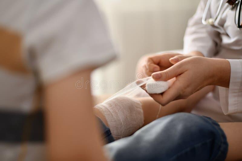 Der Doktor verbindet das Knie zum Patienten stockbild