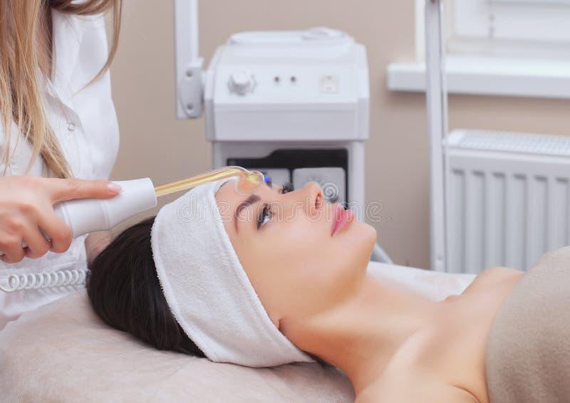 Der DoktorCosmetologist macht das Microcurrent-Therapieverfahren von einer schönen, jungen Frau in einem Schönheitssalon stockbilder