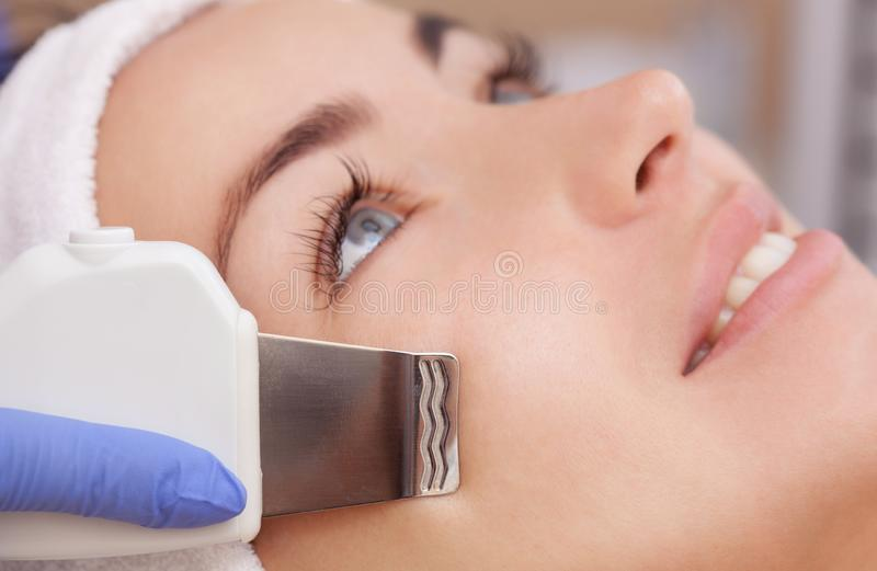 Der DoktorCosmetologist macht das UltraschallReinigungsverfahren von der Gesichtshaut einer schönen, jungen Frau lizenzfreies stockbild
