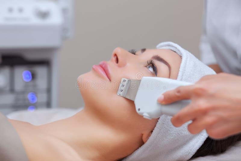 Der DoktorCosmetologist macht das UltraschallReinigungsverfahren von der Gesichtshaut einer schönen, jungen Frau in einem Schönhe stockfotos
