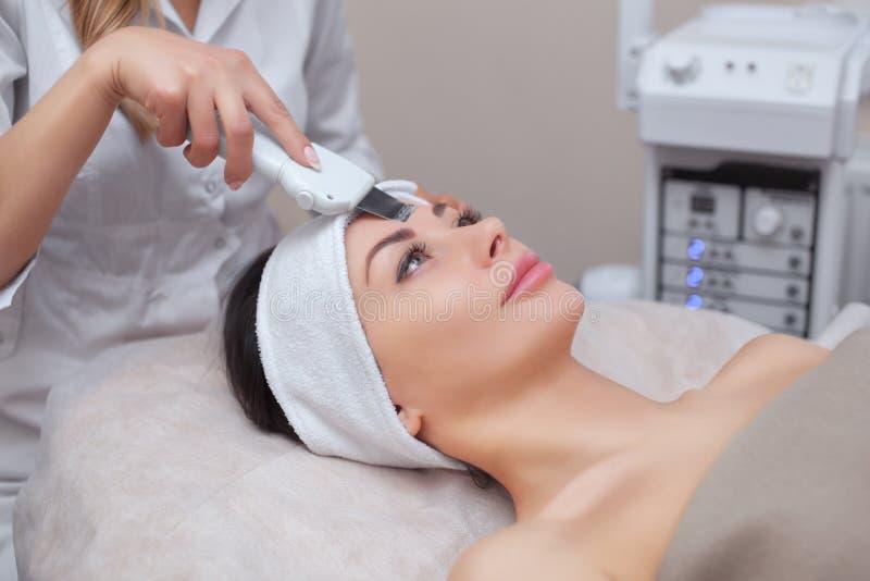 Der DoktorCosmetologist macht das UltraschallReinigungsverfahren von der Gesichtshaut einer schönen, jungen Frau in einem Schönhe lizenzfreies stockbild