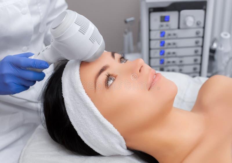 Der DoktorCosmetologist macht die Verfahren Kryotherapie von der Gesichtshaut einer schönen, jungen Frau stockbild