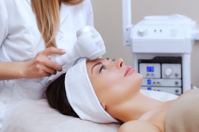 Der DoktorCosmetologist macht die Verfahren Kryotherapie von der Gesichtshaut einer schönen, jungen Frau in einem Schönheitssalon stockfotografie