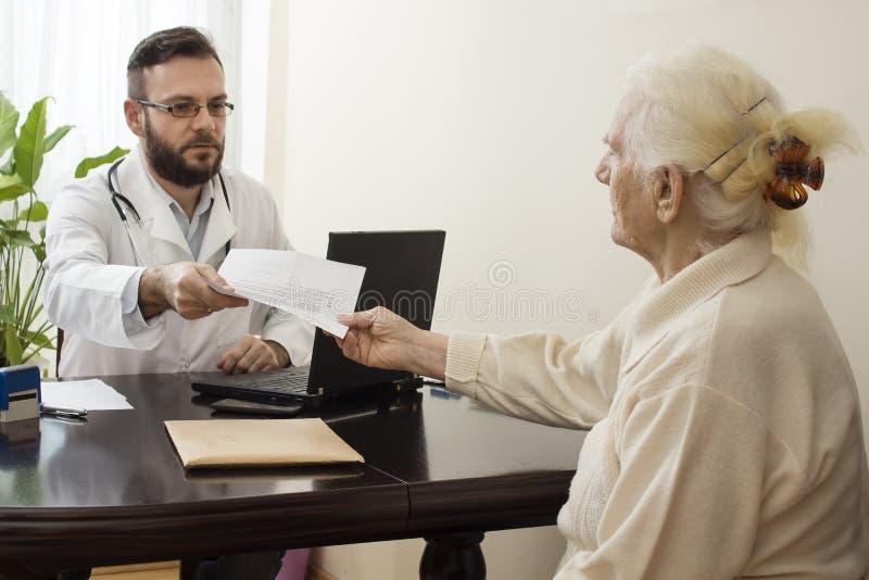 Der Doktorgeriater mit einem Patienten Empfängt Dokumente vom Patienten stockbild
