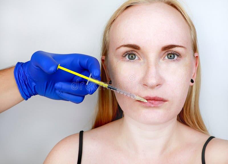 Der Doktorkosmetiker leitet Konturnplastiklippen: eine Einspritzung in die Lippen, Lippenvermehrung Hyalurons?ureeinspritzung lizenzfreie stockfotos