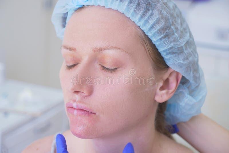 Der Doktorkosmetiker macht Einspritzungen angesichts des weiblichen Patienten Schönheitsbegriff und Cosmetology 4K lizenzfreie stockfotos