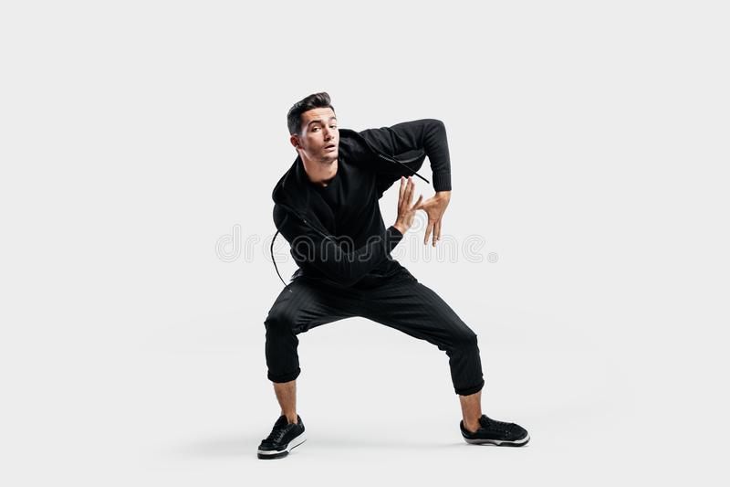 Der dunkelhaarige junge Mann, der in schwarze Kleidung gekleidet wird, tanzt Straßentanz Er macht stilisierte Bewegungen mit sein lizenzfreies stockfoto