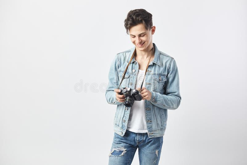 Der dunkelhaarige Kerl, der in einem weißen T-Shirt, in den Jeans und in einer Denimjacke gekleidet wird, hält Kamera n seine haa lizenzfreies stockfoto