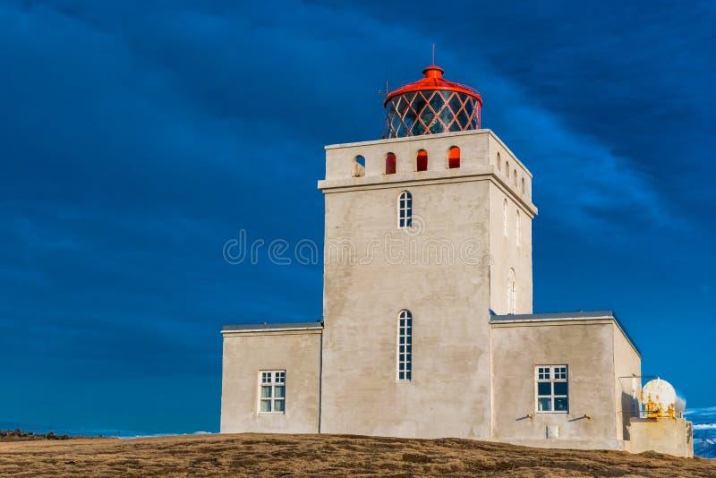 Der Dyrholaey-Leuchtturm in Island-Ständen schützen in den stürmischen Himmeln stockfotografie