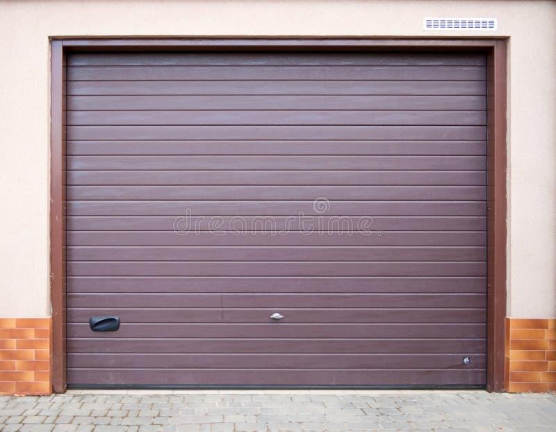Der Eingang zur Garage wird mit einem Rollenfensterladentor ausger?stet stockbilder