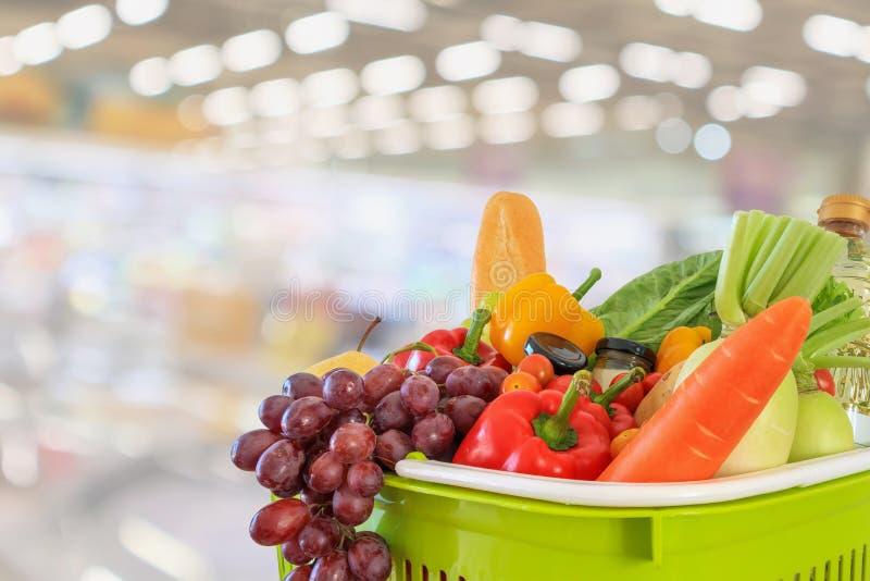 Der Einkaufskorb, der mit Obst und Gemüse mit Supermarktgemischtwarenladen gefüllt wurde, verwischte defocused Hintergrund lizenzfreie stockbilder