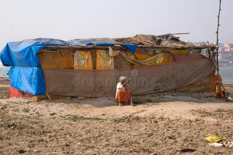 Der Einsiedler, ein sadhu, sitzt das Meditieren auf dem heiligen Fluss der Ganges lizenzfreie stockbilder