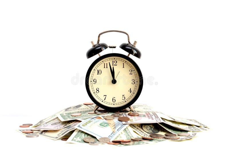 Der Einsparungen Konzept im Laufe der Zeit vorgeschlagen durch einen Retro- Wecker, der auf einen Stapel des Geldes steht stockfotografie