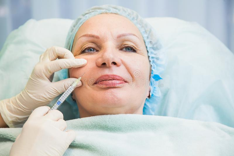 Der Einspritzungsverjüngungs-Haut der älteren Frau cosmetologic Verfahren stockfotos