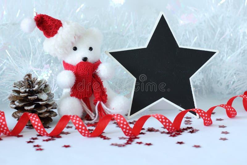 Der Eisbär, der einen Hut tragen und ein roter Schal für Weihnachtsfestdekoration mit einer Scheinmeldung planen lizenzfreie stockfotos
