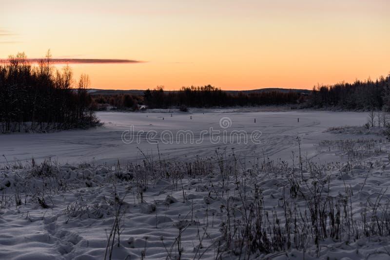Der Eissee und -wald hat mit starken Schneefällen und Sonnenunterganghimmel in der Wintersaison am Feriendorf Kuukiuru, Finnland  lizenzfreies stockfoto