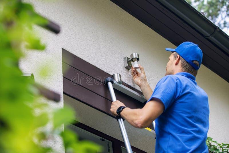 Der Elektriker, der auf Leiter steht und ändern die Glühlampe lizenzfreies stockbild