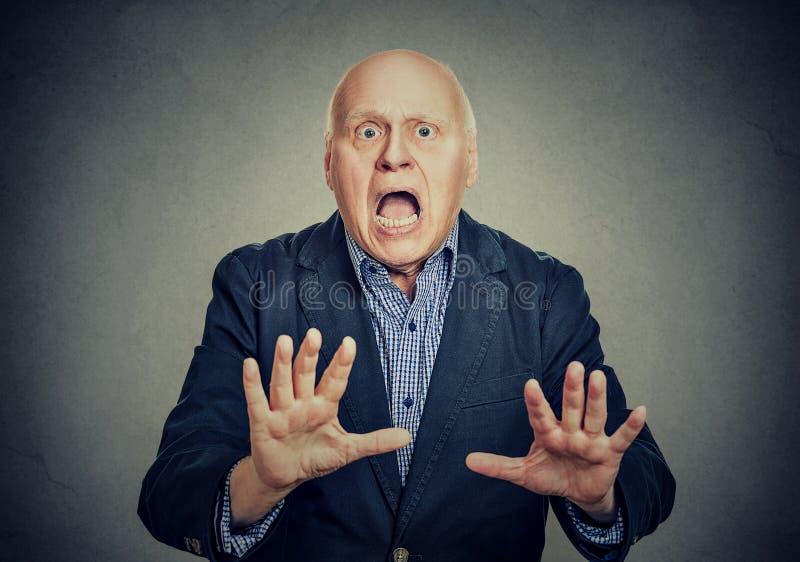 Der entsetzte ältere Mann, der seins hält, teilt in der Furcht aus lizenzfreies stockfoto