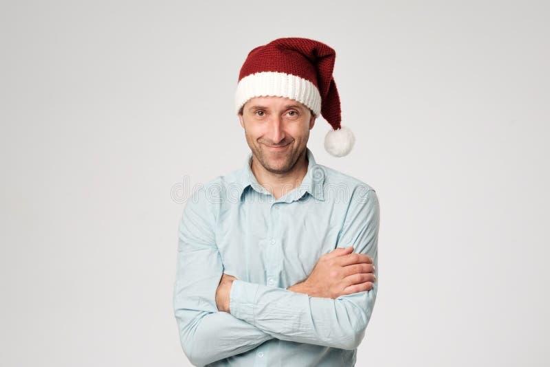 Der entspannte reife Mann, der Weihnachtsmann-Hut steht mit den Händen trägt, kreuzte auf weißem Hintergrund lizenzfreies stockbild