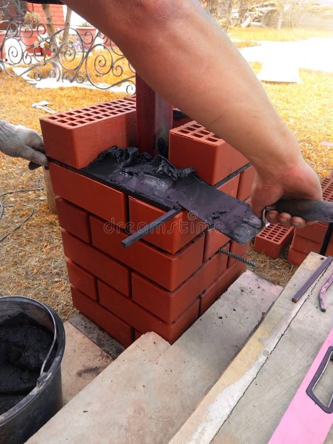 Der Erbauer benutzt eine Kelle für Maurerarbeitziegelsteine lizenzfreies stockbild