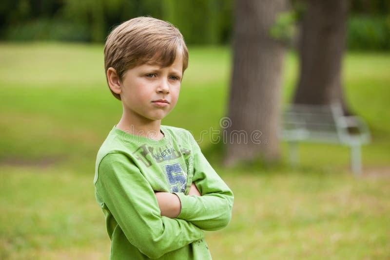 Der ernste Junge, der mit den Armen steht, kreuzte am Park stockfoto