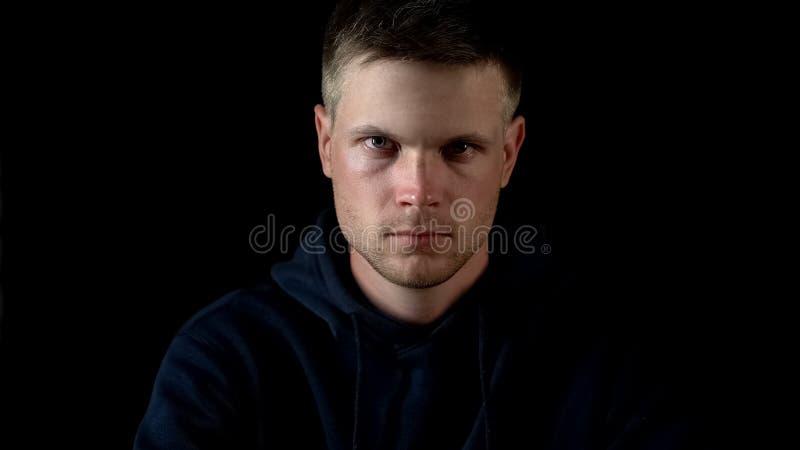 Der ernste Mann, der die Kamera, sitzend auf schwarzem Hintergrund untersucht, schließen herauf Ansicht lizenzfreie stockfotografie