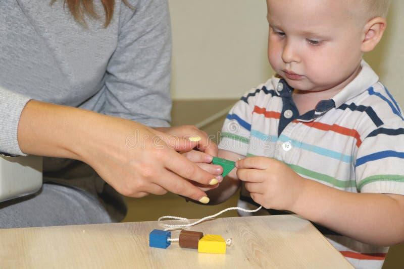 Der Erzieher beschäftigt das Kind im Kindergarten Kreativität und Entwicklung des Kindes lizenzfreies stockbild