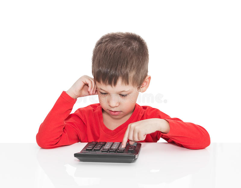 Der Fünfjahresjunge, der an einem weißen Tisch sitzt lizenzfreie stockfotografie