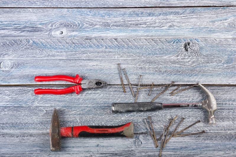 Der Fachmann, der Werkzeuge für Verzierungsund errichtende Erneuerung repariert, stellte auf den hölzernen Hintergrund ein Beschn lizenzfreie stockbilder