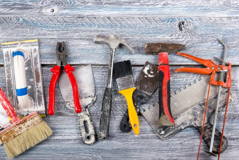 Der Fachmann, der Werkzeuge für Verzierungsund errichtende Erneuerung repariert, stellte auf den hölzernen Hintergrund ein Elektr lizenzfreies stockbild