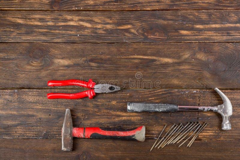 Der Fachmann, der Werkzeuge für Verzierungsund errichtende Erneuerung repariert, stellte auf den hölzernen Hintergrund ein Vergip stockfotografie