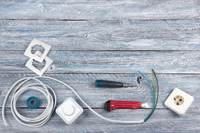 Der Fachmann, der Werkzeuge für Verzierungsund errichtende Erneuerung repariert, stellte auf den hölzernen Hintergrund, Elektrike stockbilder