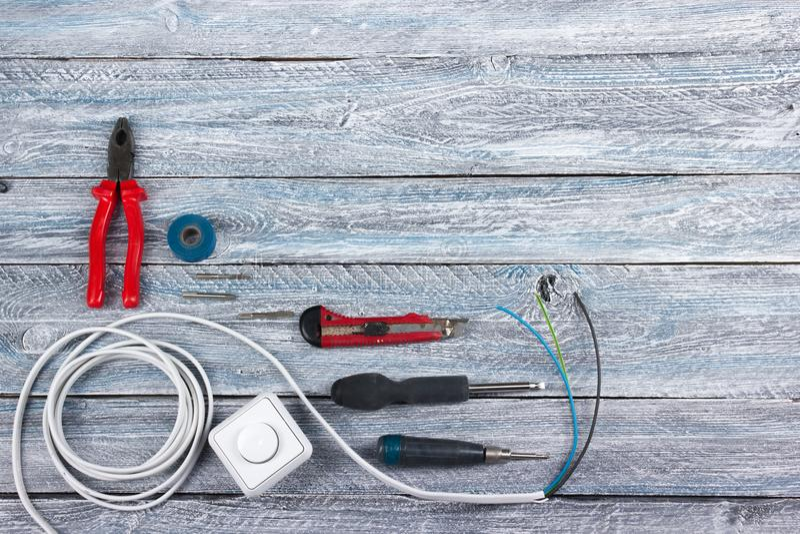 Der Fachmann, der Werkzeuge für Verzierungsund errichtende Erneuerung repariert, stellte auf den hölzernen Hintergrund, Elektrike lizenzfreies stockfoto