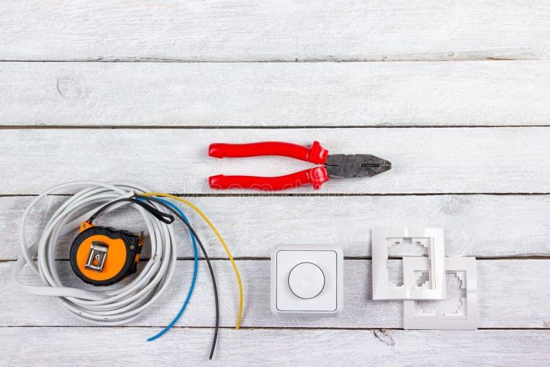 Der Fachmann, der Werkzeuge für Verzierungsund errichtende Erneuerung repariert, stellte in den hölzernen Hintergrund, Elektriker lizenzfreie stockfotos