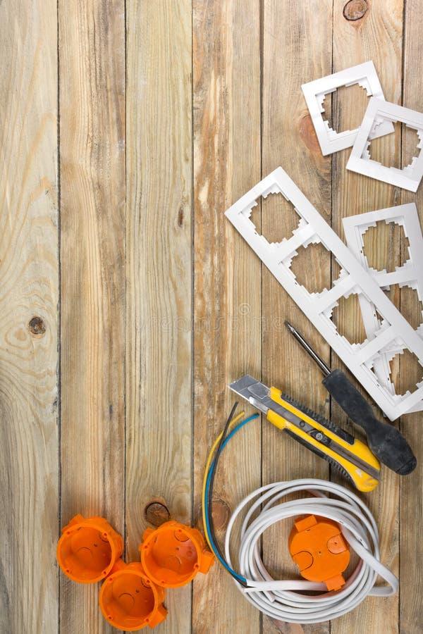 Der Fachmann, der Werkzeuge für Verzierungsund errichtende Erneuerung repariert, stellte in den hölzernen Hintergrund, Elektriker stockfoto