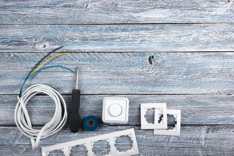 Der Fachmann, der Werkzeuge für Verzierungsund errichtende Erneuerung repariert, stellte in den hölzernen Hintergrund, Elektriker lizenzfreies stockfoto