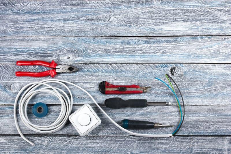 Der Fachmann, der Werkzeuge für Verzierungsund errichtende Erneuerung repariert, stellte in den hölzernen Hintergrund, Elektriker lizenzfreie stockfotografie