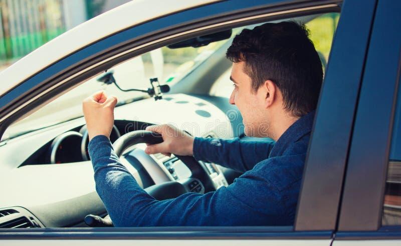 Der Fahrer des jungen Mannes, der seine Faust schreit und rüttelt, bedroht einen anderen Kraftfahrer stockfotografie