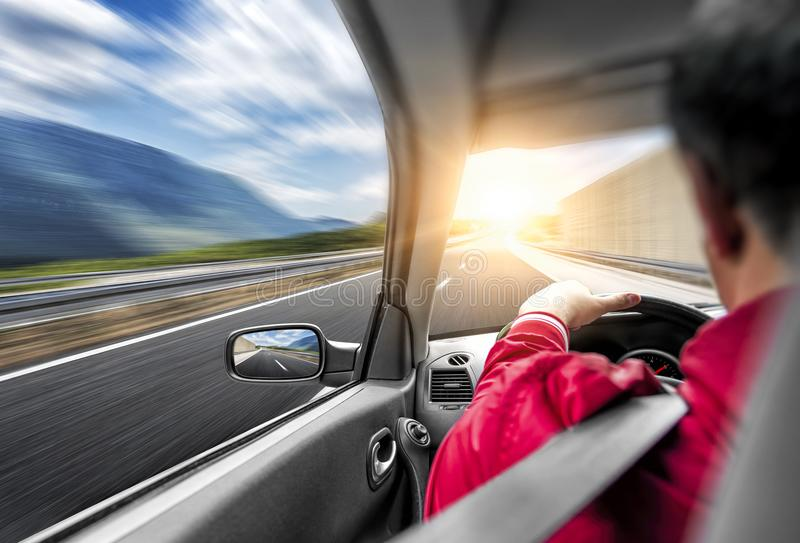 Der Fahrer hetzt mit dem Auto entlang der Straße Geschwindigkeitsrennen in der Bewegung stockfotos