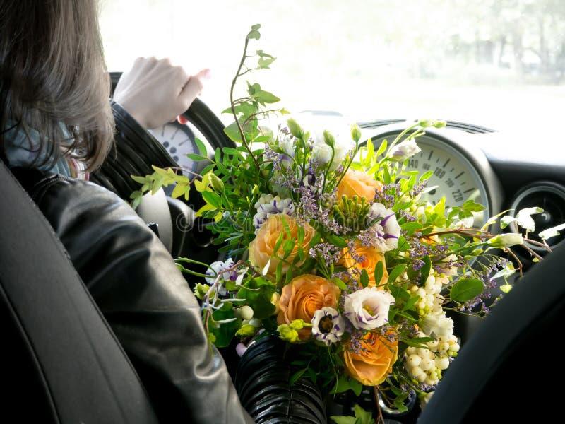 Der Fahrer hinter dem Rad mit einem Blumenstrauß von Blumen lizenzfreies stockbild