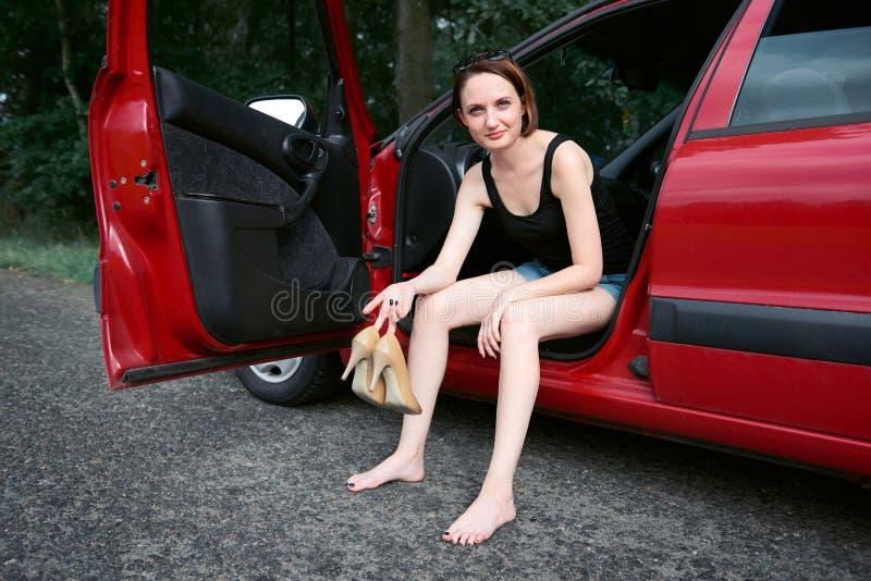 Der Fahrer der jungen Frau, der in einem roten Auto stillsteht, entfernen ihre Schuhe, glückliches Reisekonzept, Frauen, ` s, den lizenzfreie stockfotos