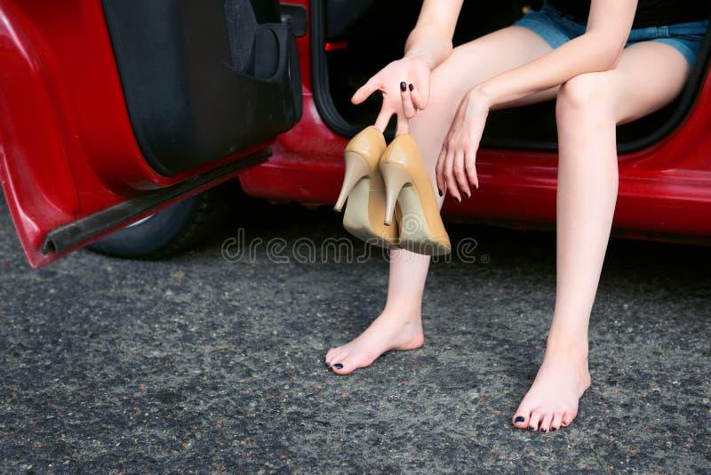 Der Fahrer der jungen Frau, der in einem roten Auto stillsteht, entfernen ihre Schuhe, glückliches Reisekonzept, Frauen, ` s, den stockbilder