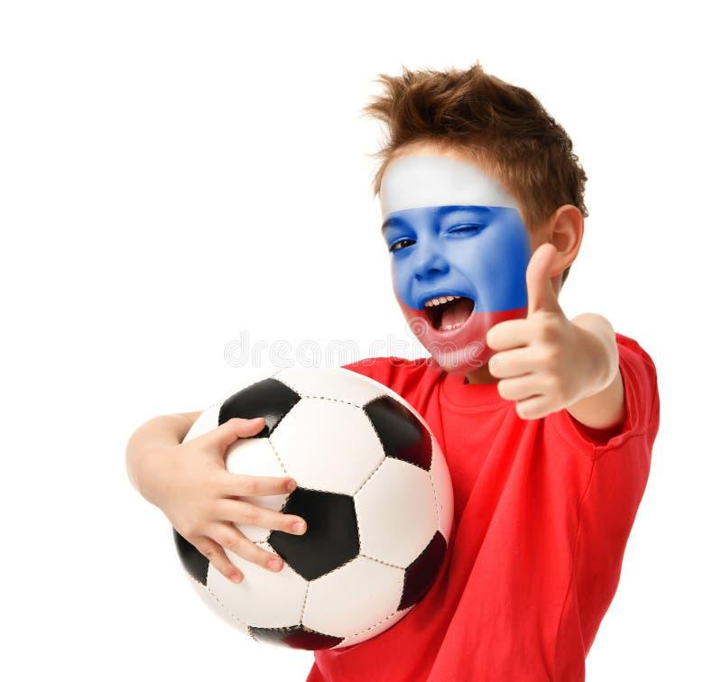 Der Fanjungenspieler-Grifffußball, der das glückliche lachende Darstellen feiert, greift herauf Zeichen mit russischer Flagge auf lizenzfreies stockfoto