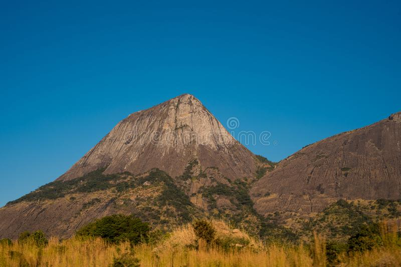 Der felsige und konische Berg erhebt sich steil von den Grasflächen stockfoto