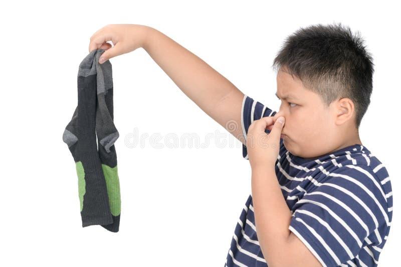 Der fette Junge, der schmutzige stinky Fußballsocken hält, lokalisierte stockbild